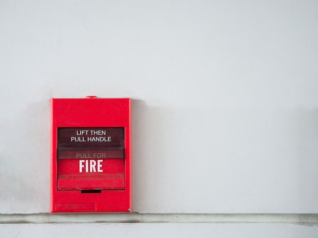 Push button switch, fire alarm on grey wall for alarm and security system with fire exting