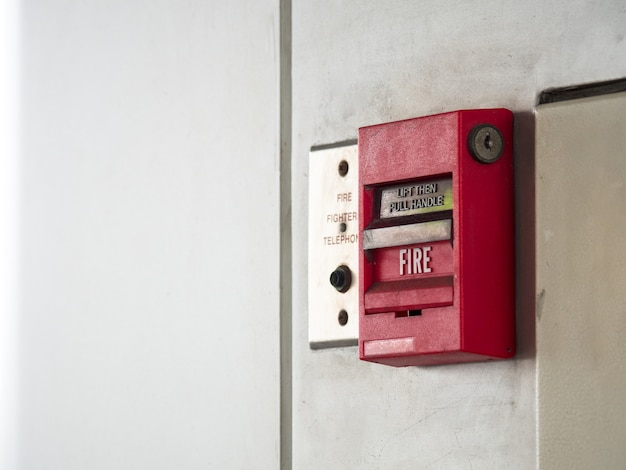Push button switch fire alarm on grey wall for alarm and security system with fire extinguer