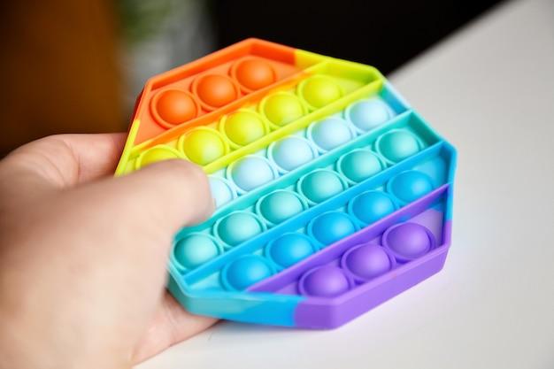 男性の手でポップバブル感覚そわそわおもちゃを押す