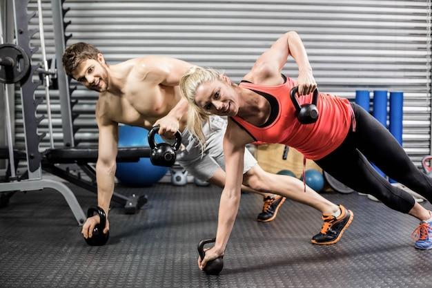 Пара делает push up с гантелями в тренажерном зале crossfit
