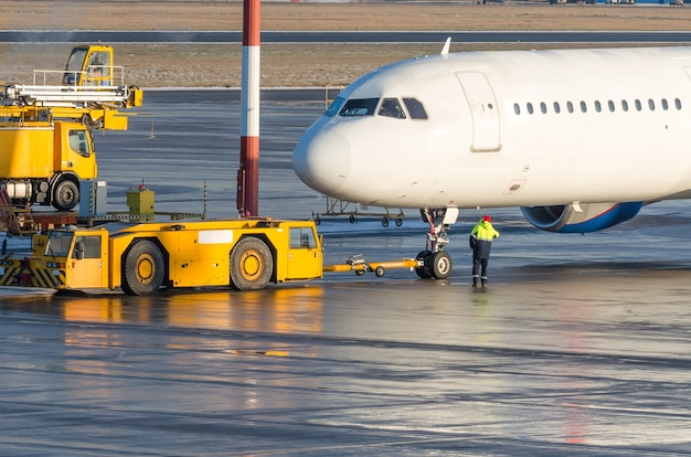 The pushback tractor is towing the aircraft to a parking lot, aviation marshall.