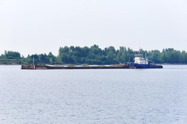 プッシャータグボートは、川の砂で乾いたバルク貨物バージを押します