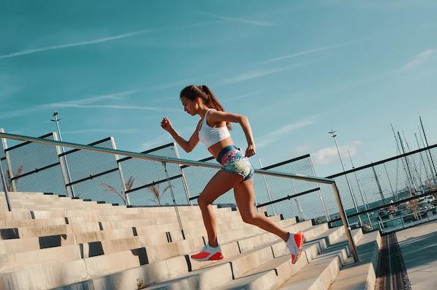 強く押す。屋外で運動しながら走っているスポーツウェアの美しい若い女性の全長