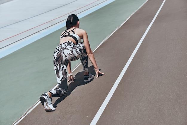 Тяжело давить. вид сверху сзади молодой женщины в спортивной одежде, стоящей на стартовой линии
