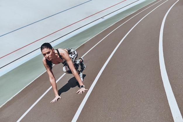 Доводя себя до предела. вид сверху молодой женщины в спортивной одежде, стоящей на стартовой линии