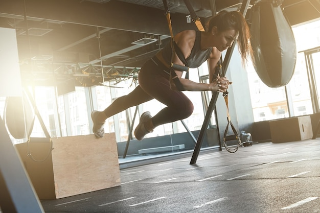 Pushing the limits. young athletic strong woman in sportswear doing trx workout at industrial gym, exercising with fitness straps. suspension training concept. sport, wellness and healthy lifestyle