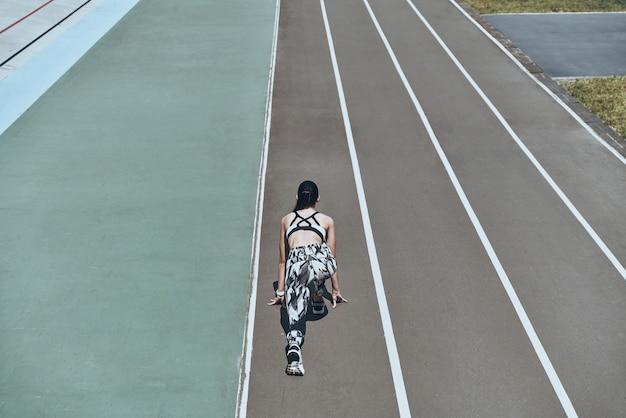 Работаем до предела. вид сверху сзади молодой женщины в спортивной одежде, стоящей на стартовой линии