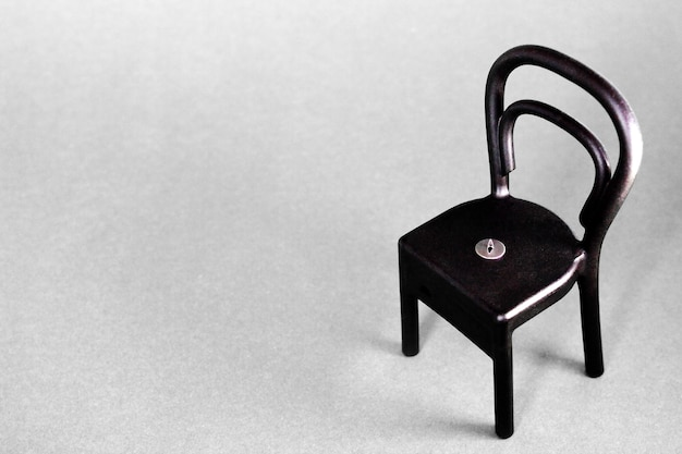A pushpin on the black plastic chair on gray