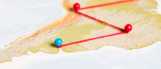 Pushpins with thread on route map