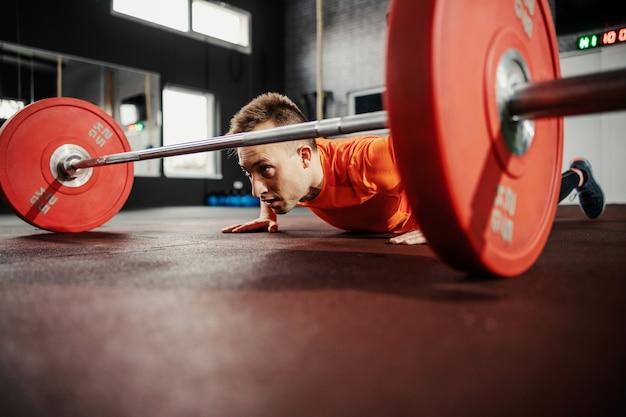 腕立て伏せと筋肉強化スポーティな筋肉質の男性がジムでバーベルの後ろで腕立て伏せをします