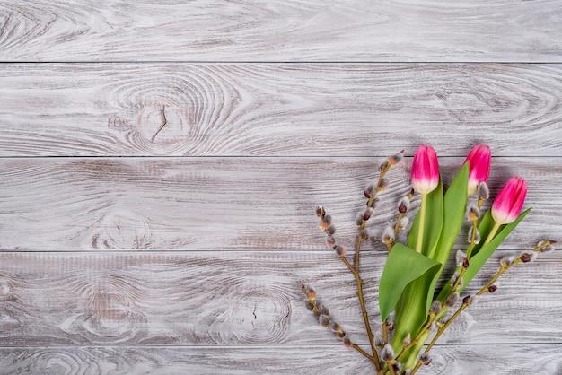 Верба, перепелиные яйца, желтые цветы тюльпанов на светло-сером бетонном фоне. понятие праздника весны и пасхи. плоская планировка, вид сверху, копия пространства.
