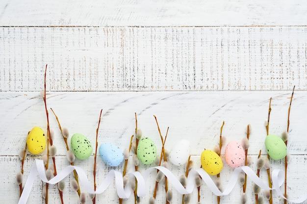 갯버들 가지와 다채로운 부활절 달걀. 평평하다.
