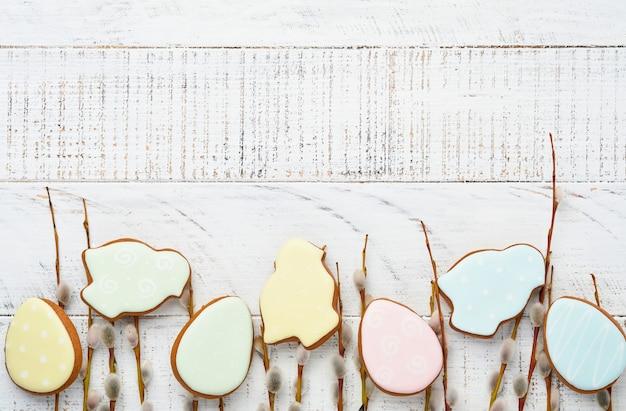 갯버들 가지와 다채로운 부활절 진저 토끼, 계란 및 닭 흰색 오래 된 나무 테이블에. 평평하다.