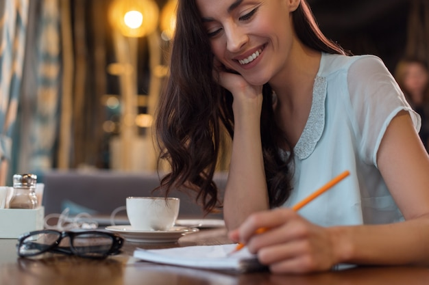 Put it down. cheerful merry thoughtful woman grinning while writing down plan and drinking coffee
