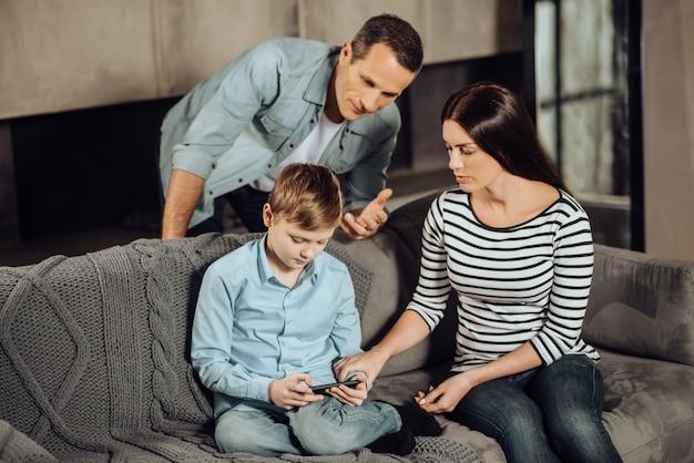 내려 놔. 소년이 주저하는 동안 십대 전 아들에게 전화 게임을 그만두도록 설득하려는 즐거운 젊은 부모