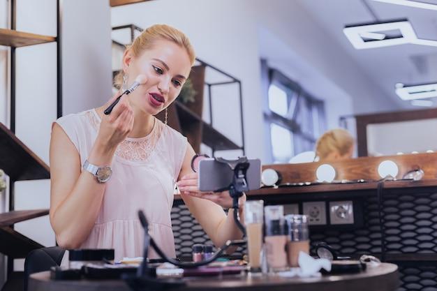 化粧をします。カメラの前で彼女の化粧をしている美しい若いブロンドの髪の女性