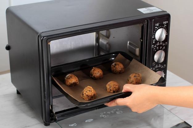 チョコチップクッキーのすくい取った生クッキー生地をオーブンに入れます。焼く準備ができている黒いトレイのクッキー生地。女性のパン屋の手に焦点を当てる