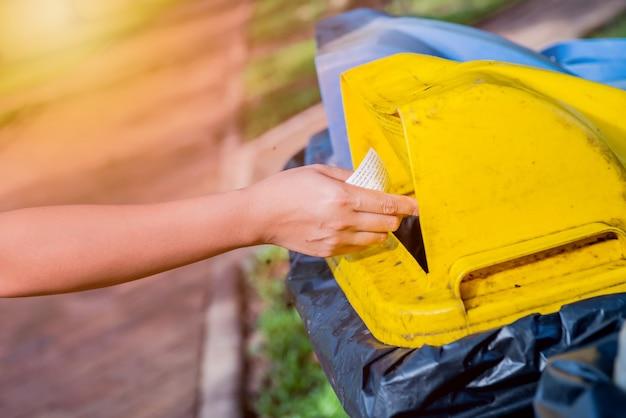 Поместите мусор в мусорное ведро в парке