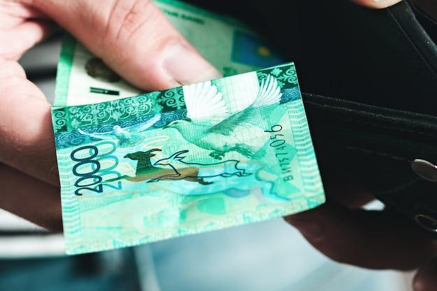 Кладет деньги в мужской кошелек. банкнота достоинством две тысячи тенге.