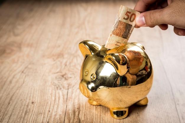 Putting a 50 reais into a piggy bank