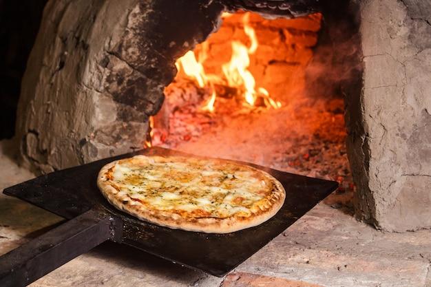 パラグアイの手作りオーブン(タタクア)に4チーズのピザを入れます。