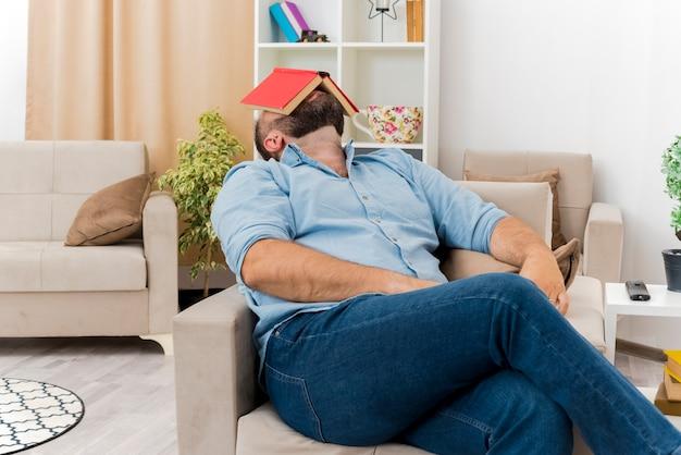 Mettere l'uomo slavo adulto si siede sulla poltrona che tiene il libro sul viso all'interno del soggiorno