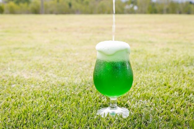 성 패트릭의 날을 위해 유리 잔에 맥주를 넣기. 잔디밭에서.