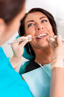 Надевание зубных скобок на зубы женщины в стоматологическом кабинете. стоматолог изучить пациентки с брекетами в стоматологическом кабинете. крупный план молодой привлекательной девушки с брекетами на зубах