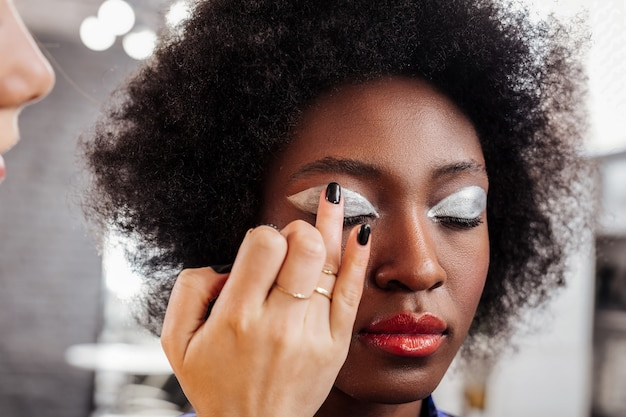 Putting eyeshadows. fair-haired young stylist wearing black nail polish working with the model