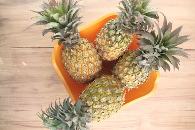 Putting fresh pineapple in bowl on table