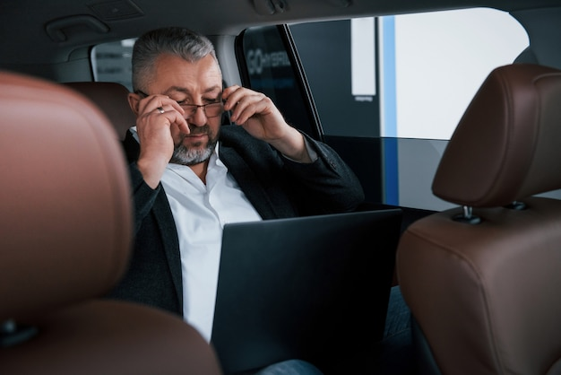Putting on glasses. working on a back of car using silver colored laptop. senior businessman