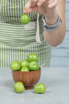Putting green cherry plums into a wooden bowl
