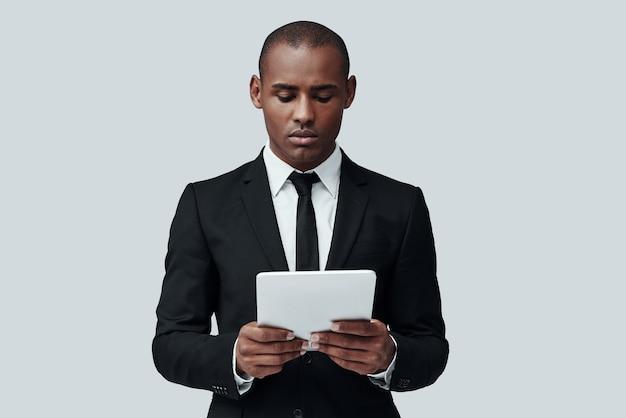 아이디어를 현실에 적용하는 것. 회색 배경에 서 있는 동안 디지털 태블릿을 사용하여 작업하는 정장 차림의 사려 깊은 아프리카 남자