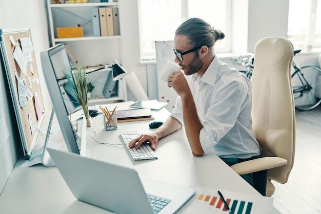Воплощение идей в реальность. вдумчивый молодой человек в рубашке работает с компьютером и пьет кофе, сидя в офисе