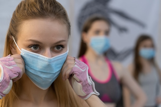 Putting on medical face protective mask athletic girls in sports outfits