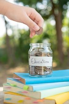 개념 투자 뮤추얼 펀드 금융 및 비즈니스를위한 유리 병에 돈 동전을 넣어 교과서에 배치합니다. 교육을위한 콘텐츠 비용 절감.