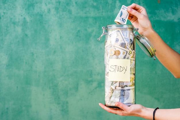 녹색 벽 배경에 대한 연구를 위해 저축한 돈을 병에 넣습니다. 복사 공간이 있는 이미지