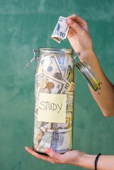 녹색 벽 배경에 대한 연구를 위해 저축한 돈을 병에 넣는 것