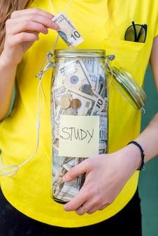 노란색 티셔츠 배경에 대한 연구를 위해 저축한 돈을 병에 넣는 것