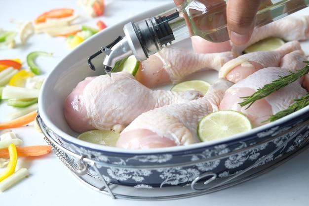 生の鶏肉のドラムスティックにオリーブオイルを塗る