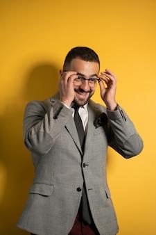 Надев очки, красивый улыбающийся элегантный мужчина в строгом сером пиджаке с поднятыми обеими руками стоит немного боком, изолированным на желтой стене