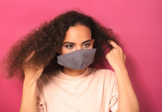 Надевание многоразовой маски на лицо очаровательная афроамериканка в персиковой футболке