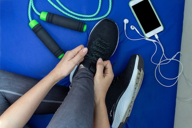 집에서 훈련하기 위해 테니스를 치고 파란색 매트에 옆에 밧줄과 휴대 전화