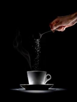 Putting sugar in the coffee