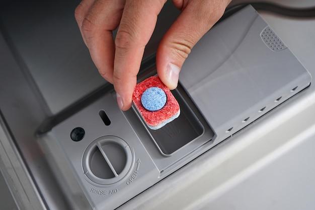 食器洗い機にタブを入れて、クローズアップ。食器洗い機用洗剤のタブレットを持っている男の手。