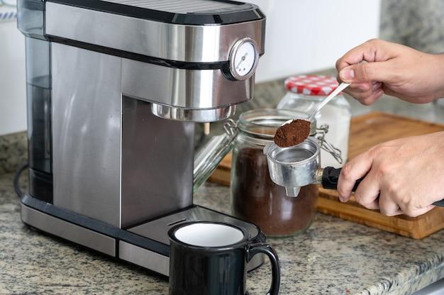 自宅でコーヒーを入れるためにスプーンでフィルターにコーヒーを入れます。