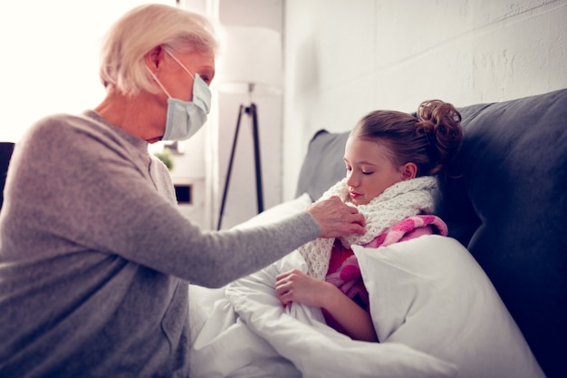 Putting warm scarf. caring granny wearing protective mask putting warm scarf on her cute girl after catching cold