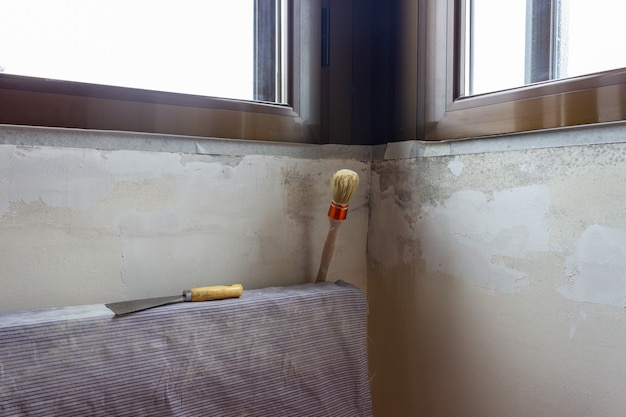 A putty knife and a paint brush on a radiator ready to fix the wall.indoor