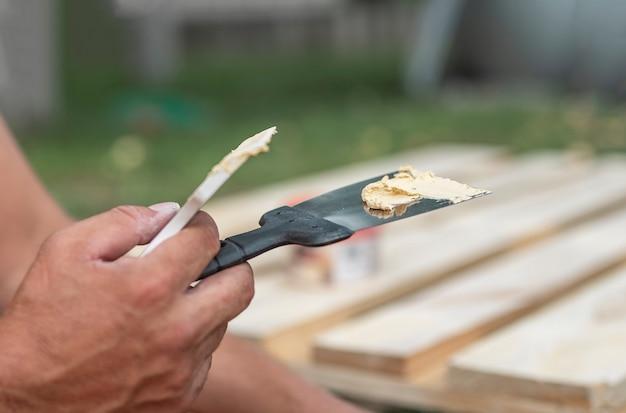 Замазка на шпатель в мужских руках крупным планом, ремонтируя дерево с пастой