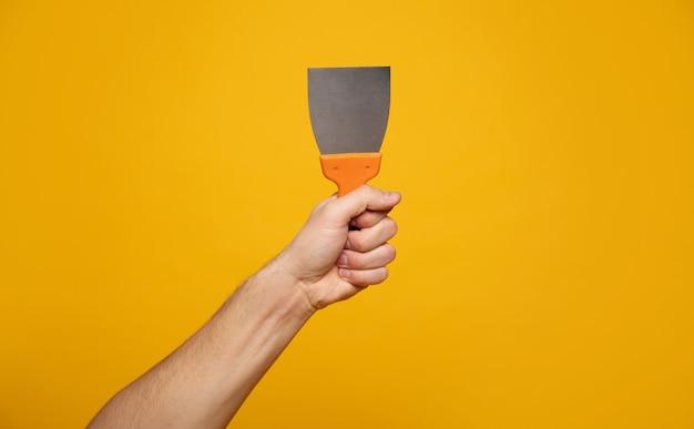 퍼티 스크레이퍼. 노란색 배경에 퍼티 스크레이퍼를 들고 손의 클로즈업 사진. 홈 리노베이션 개념.
